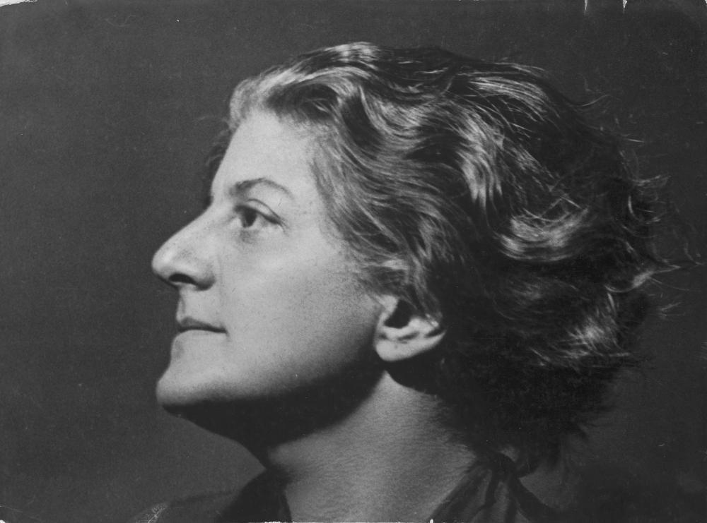 Zu sehen ist ein Selbstporträt im Querformat als Schwarzweißfotografie der deutsch-jüdischen Fotografin Gerty Simon. Es zeigt ihren Kopf im linken Profil, sie blickt nach Links oben. Sie hat kurze wellige Haare, die zurückgekämmt sind, und sie lächelt leicht.