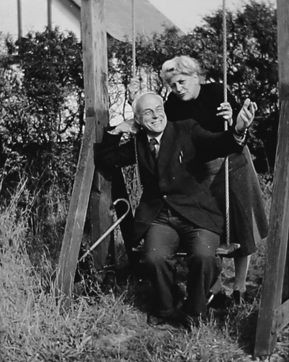 Zu sehen ist ein älteres Paar in einem Garten. Der Mann sitzt auf einer Schaukel, hat einen Anzug an und lächelt sehr stark.Dahinter steht eine Frau, die sich an der Schaukel festhält und zum Mann nach vorne neigt. Ihr Mund ist zu einer Sprechgeste verzogen. In der linken Hand hält sie eine Zigarette. Sie trägt einen dunklen Pollover und einen Rock. Ihre grauen Haare sind in einer Hochsteckfrisur. Beide sehen sehr glücklich aus.