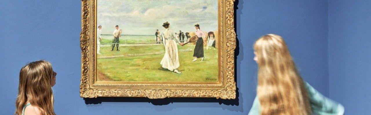 """Ausstellungsansicht """"10 Jahre MKdW – Meisterwerke"""", Museum Kunst der Westküste. Zwei Mädchen stehen links und rechts neben dem Gemälde der Tennisspielerinnen von Max Liebermann."""