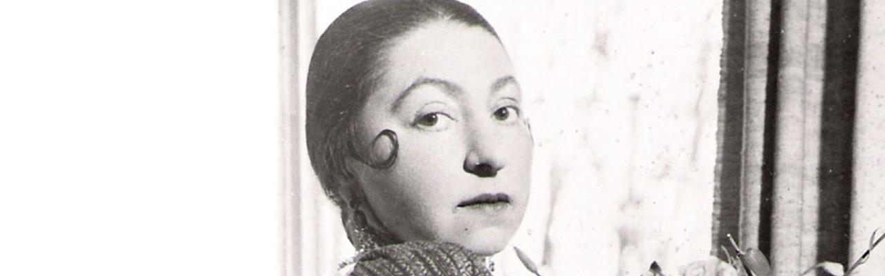 Schwarzweiß Porträt einer jungen Frau, die in die Kamra blickt.
